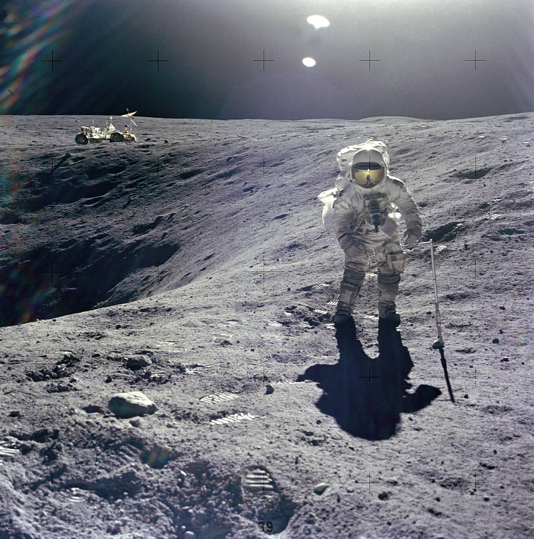 A photo of Lunar Module (Orion) pilot Charles Duke, Jr. at the rim of Plum crater.