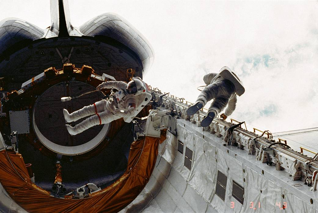 Astronauts on tethered spacewalk in cargo bay of space shuttle