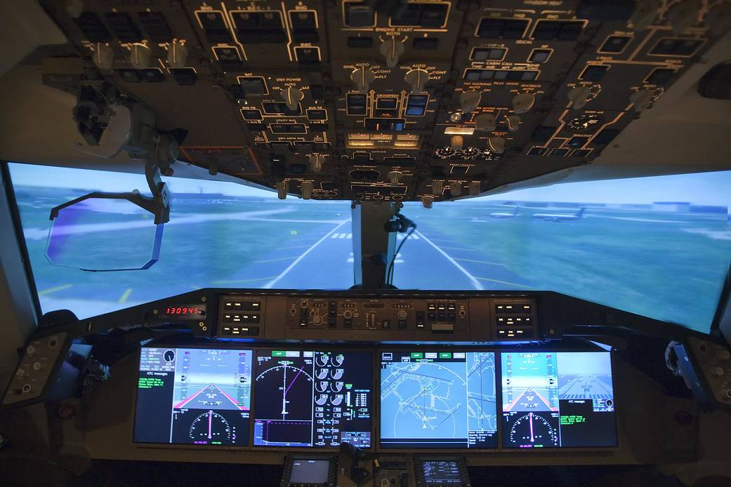 View from inside cockpit of aircraft with instrument panels surrounding and runway ahead