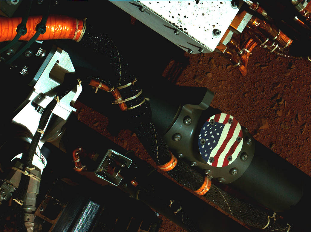 The U.S. flag on Mars - No manned missions to Mars occurred, yet, so there is no flag planted on Mars. But the Mars Rover, Curiosity, has a U.S. flag medallion affixed to a rocker arm.  From NASA: This view of the American flag medallion on NASA's Mars rover Curiosity was taken by the rover's Mars Hand Lens Imager (MAHLI) during the 44th Martian day, or sol, of Curiosity's work on Mars (Sept. 19, 2012). The flag is one of four