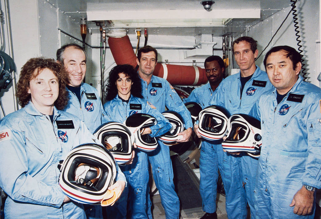 STS-51L crewmembers photographed in flight suits with helmets during a break in astronaut training.