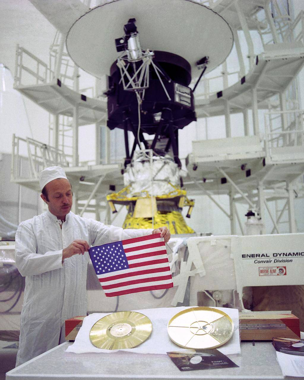Technician holds American flag in front of Voyager spacecraft and Golden Record with case