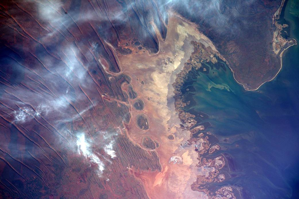 Coast of Australia with clouds overhead and colorful streaked terrain