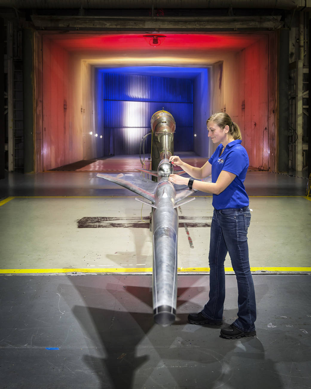 Engineer stands with X-plane design model in wind tunnel