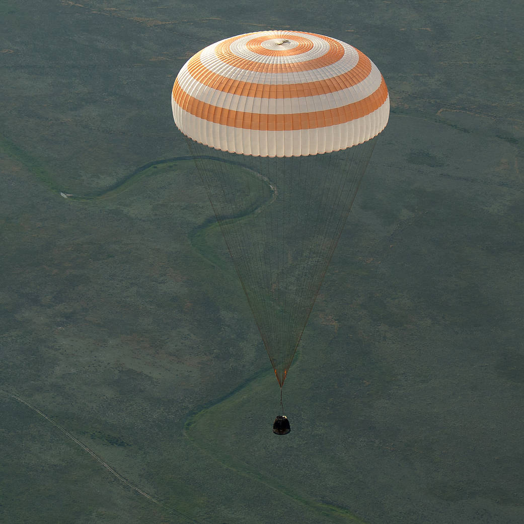 Soyuz capsule descending toward Earth with large parachute overhead