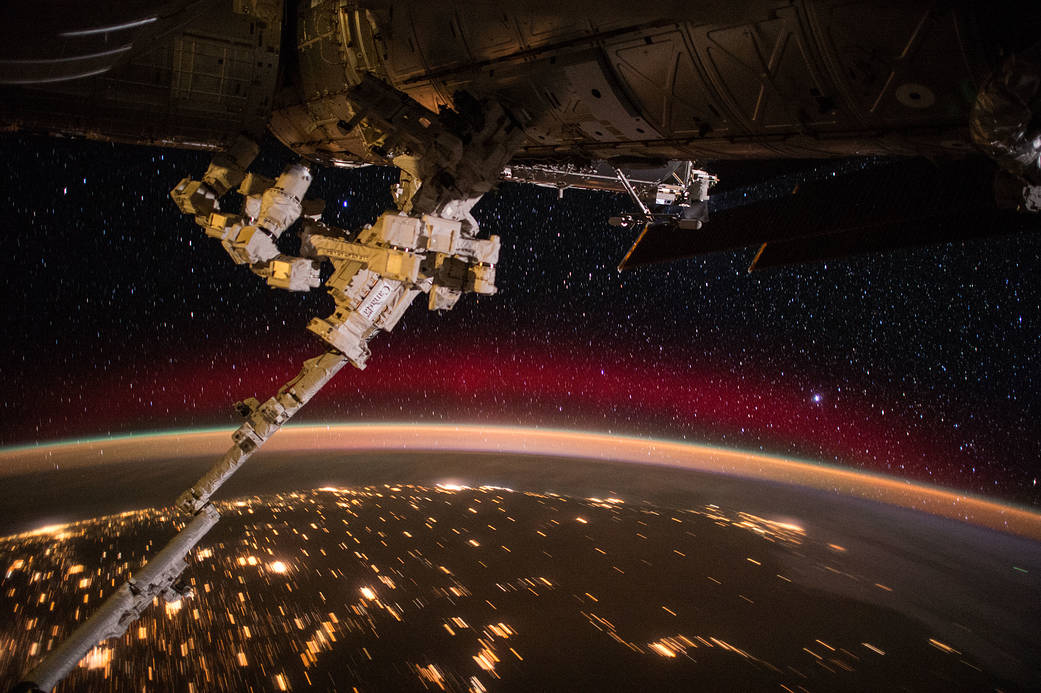 Space station robotic arm with curve of Earth and nighttime lights and aurora below