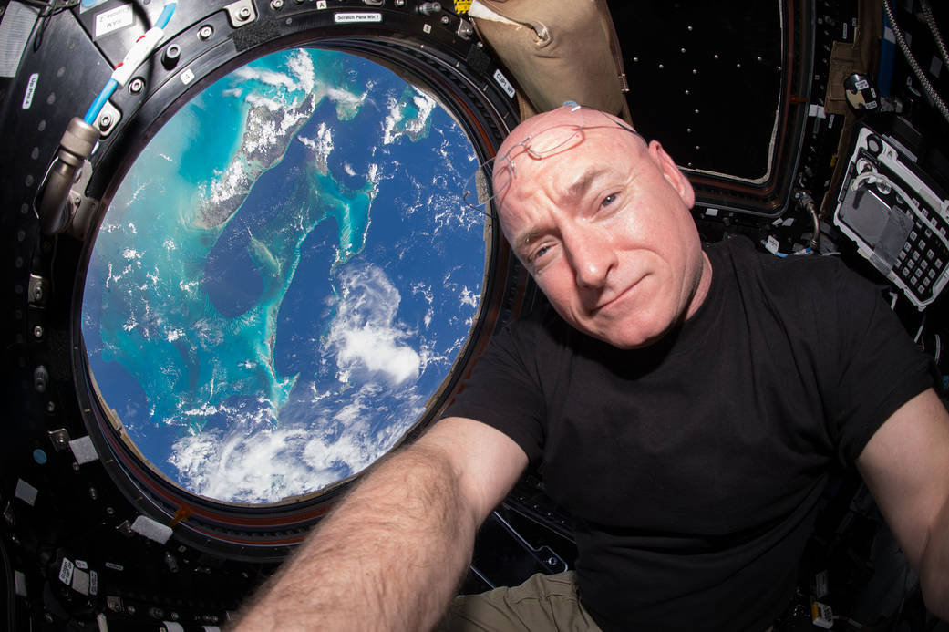 NASA astronaut Scott Kelly in the Cupola of the International Space Station with blue water of Earth visible through window