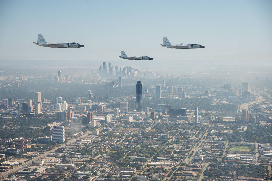Three WB-57s flying over fog with skyscrapers of downtown Houston in background