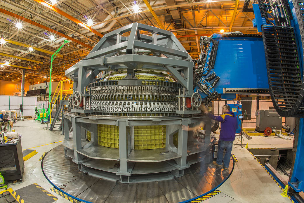 Orion spacecraft structure inside large room with engineer standing at right
