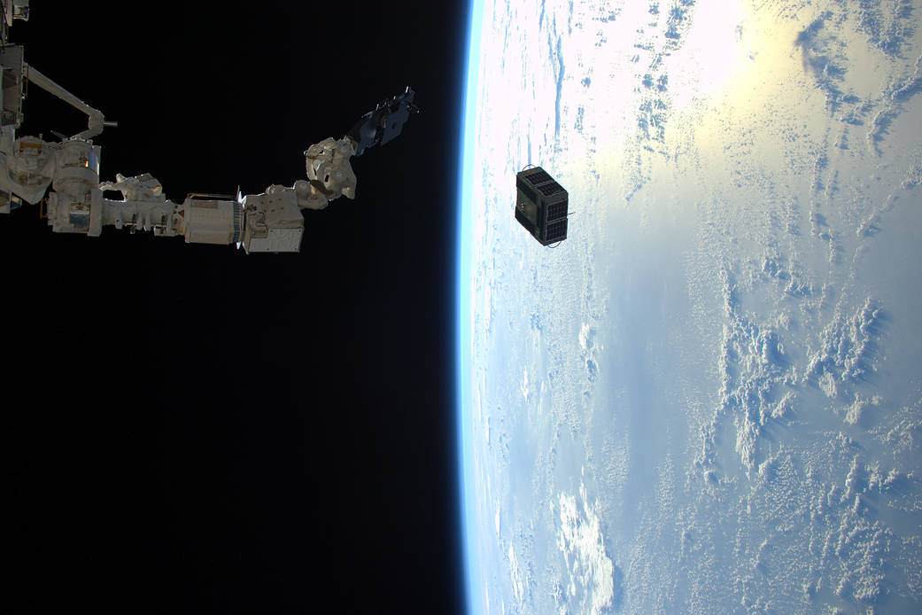 Small cube shaped satellite deployed from robotic arm with Earth visible far below