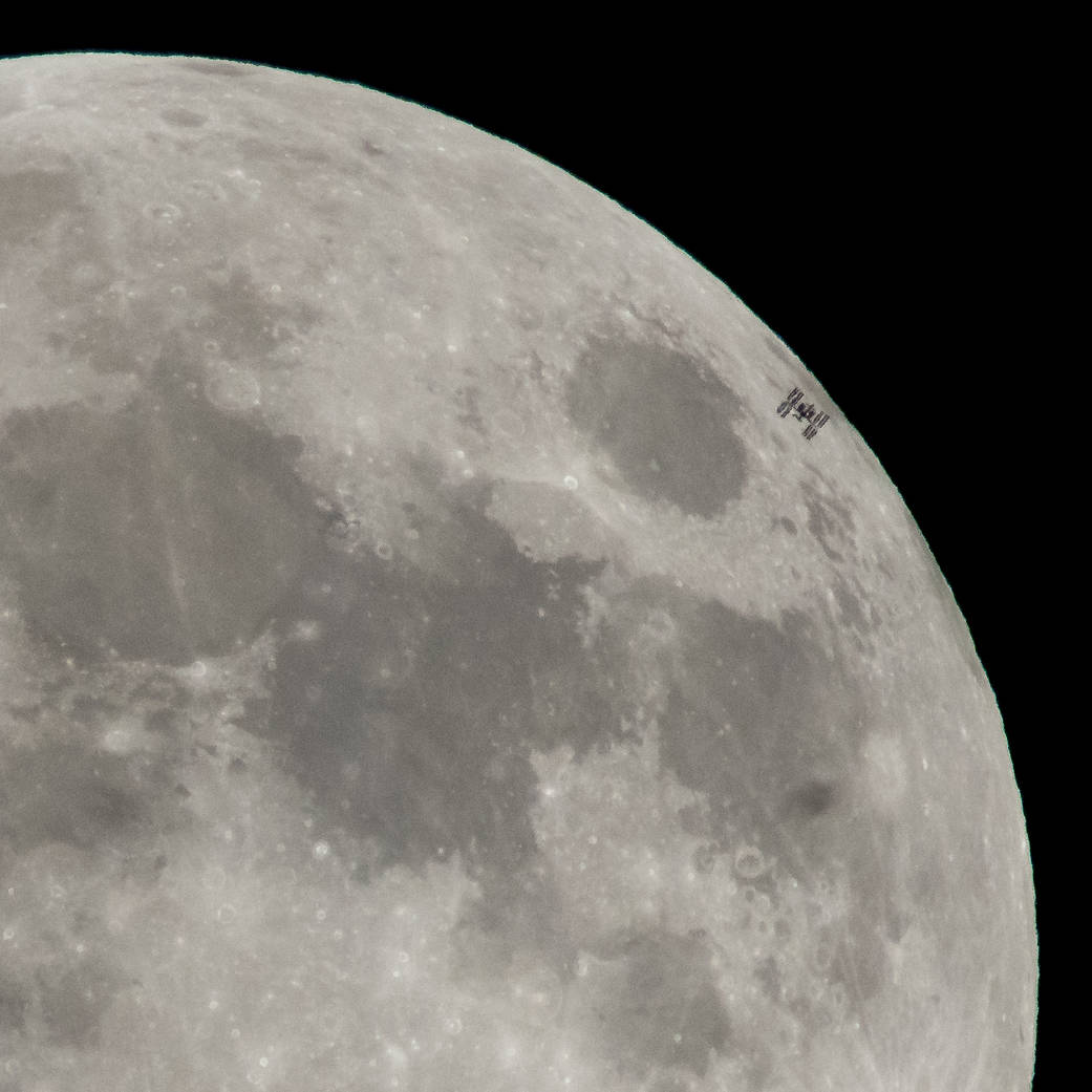 The International Space Station, with a crew of six onboard, is seen in silhouette as it transits the moon at roughly five miles