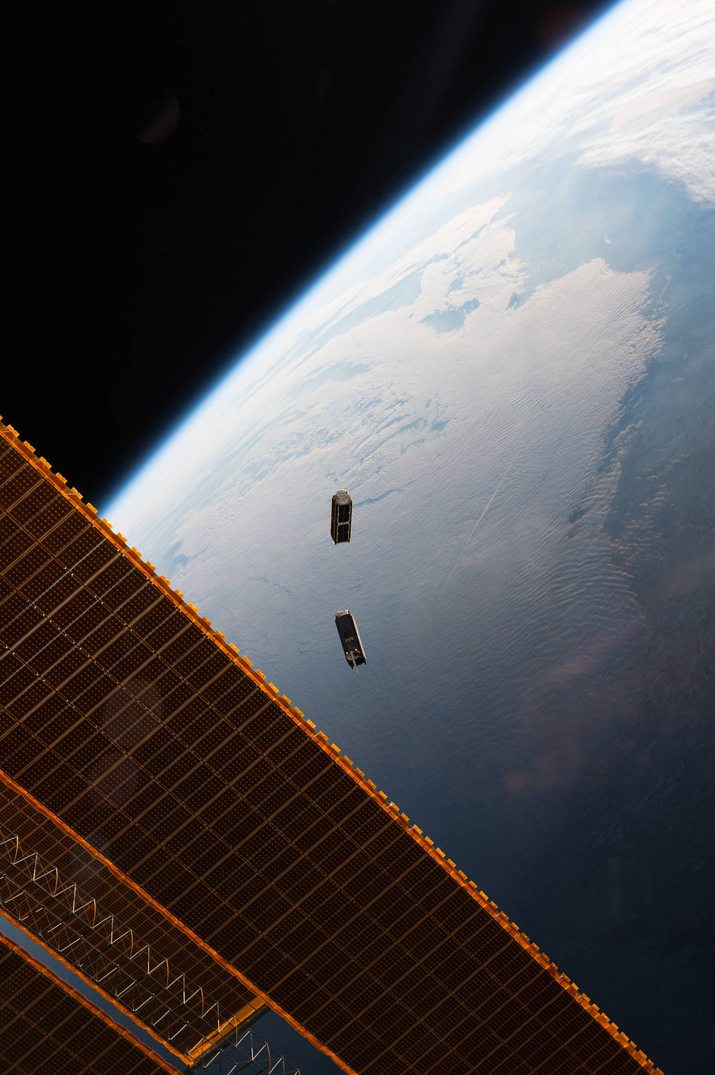 Two Cubesats in space moments after release with space station solar array visible and Earth below