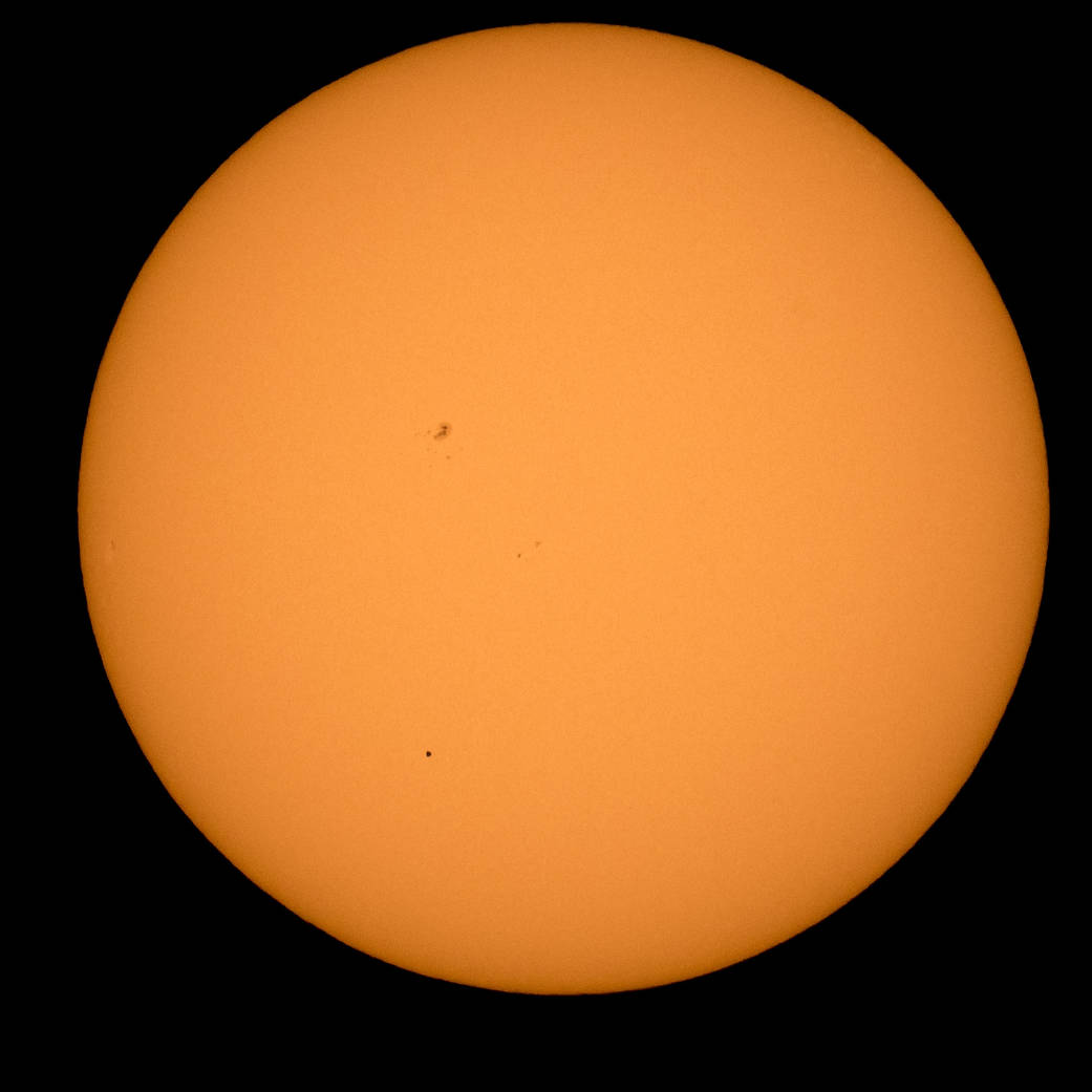 Full disc of the sun with tiny dot of planet Mercury visible as it travels across