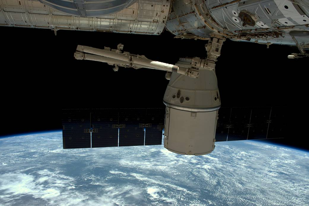 Dragon spacecraft undocking from space station with Earth visible below