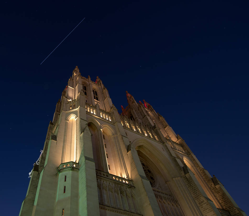 Streak of light in sky above cathedral