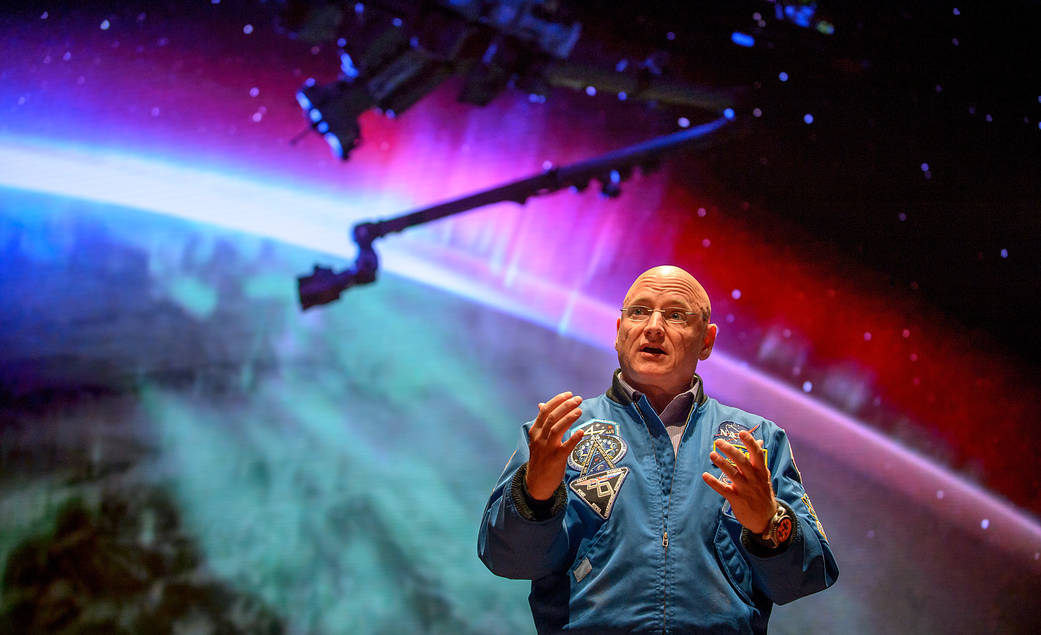 Former NASA astronaut Scott Kelly speaks at event, with backdrop showing photograph of aurora from space