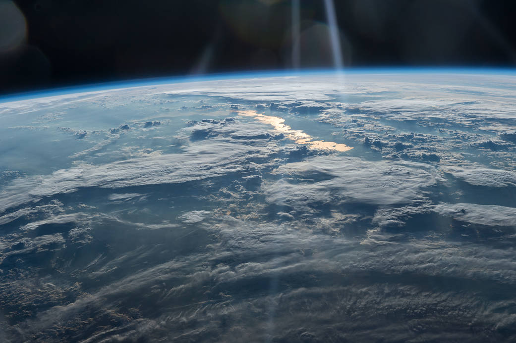Clouds and golden sun glint photographed from low Earth orbit