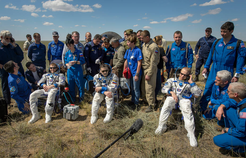 Three Expedition 47 crew members in Sokol suits seated, surrounded by officials, following landing