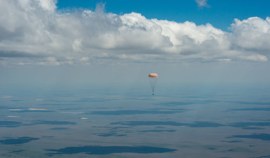 Soyuz capsule with parachute deployed descends through clouds