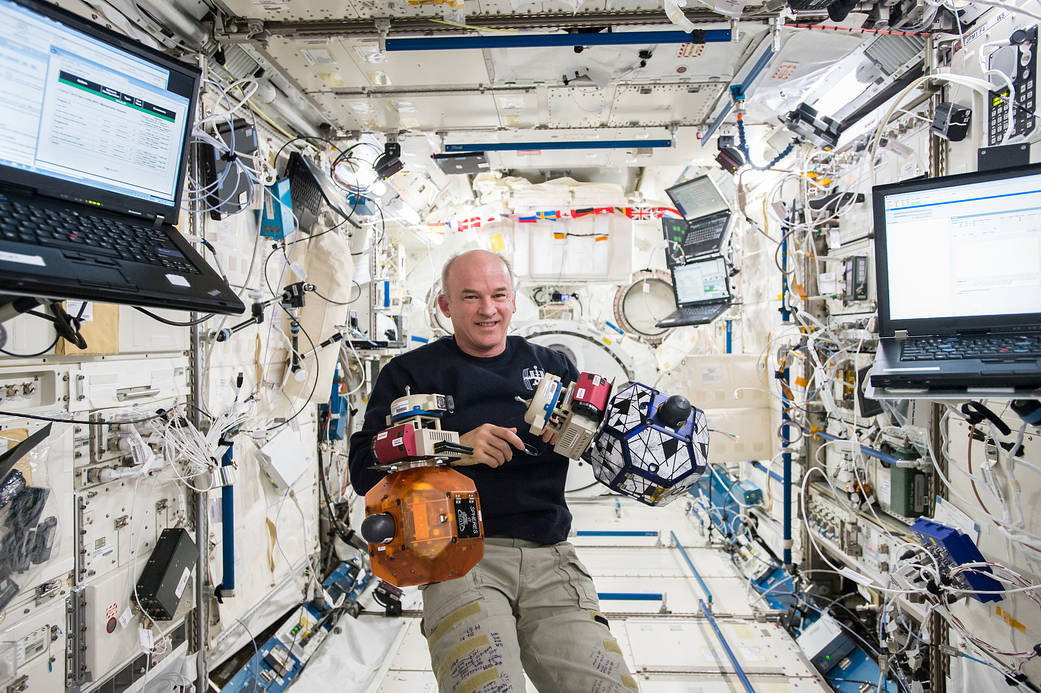 Astronaut Jeff Williams inside space station's Kibo Laboratory with floating SPHERES satellites