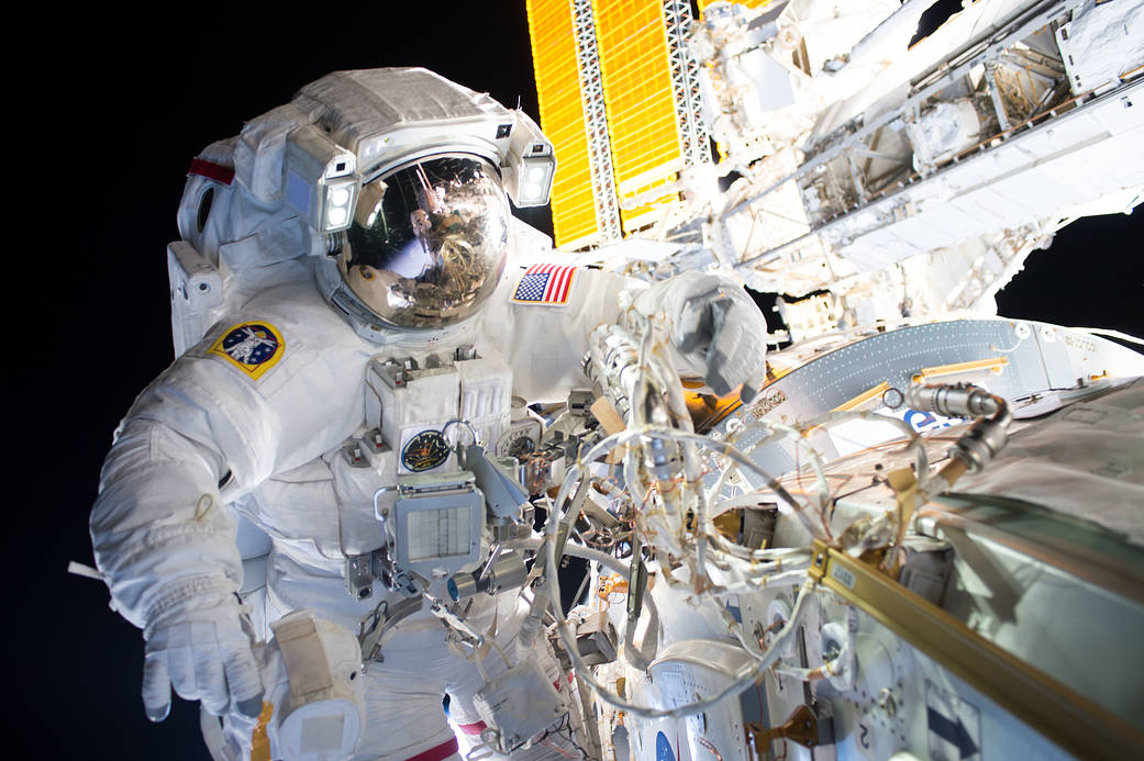 Astronaut in spacesuit working outside space station with solar array in background
