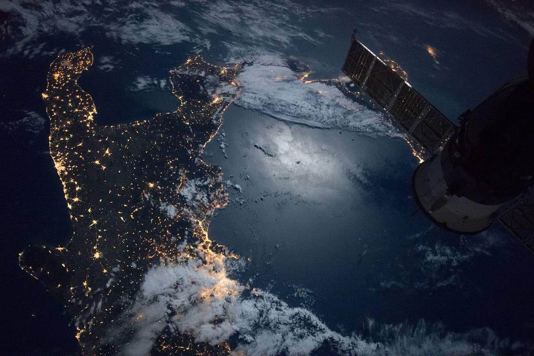 Nighttime view of southern Italy with glint on water from moonlight, taken from low Earth orbit