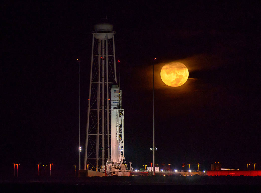 The Orbital ATK Antares rocket, with the Cygnus spacecraft onboard, is seen on launch Pad-0A as the moon sets, predawn, Saturday