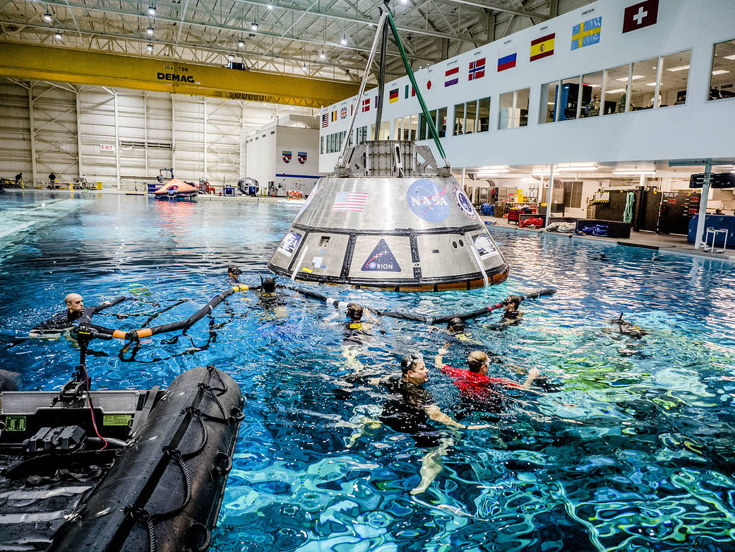 Orion spacecraft in large pool with divers