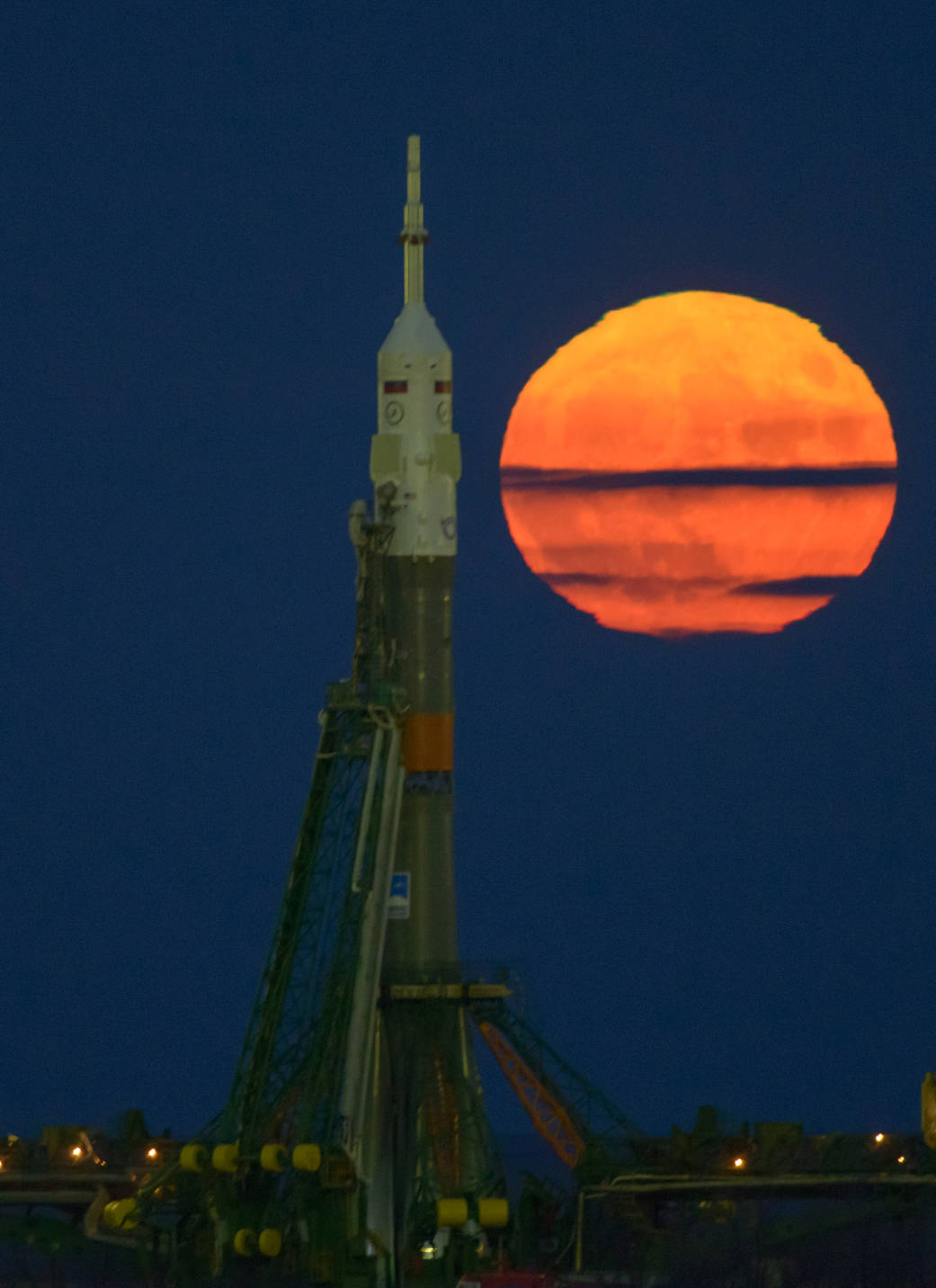 Moon rising at left and Soyuz rocket at launchpad