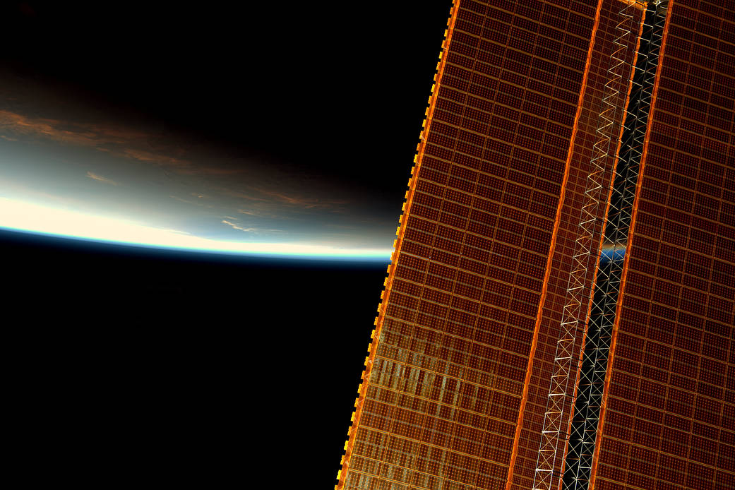 Sunrise over Earth's horizon with space station solar array