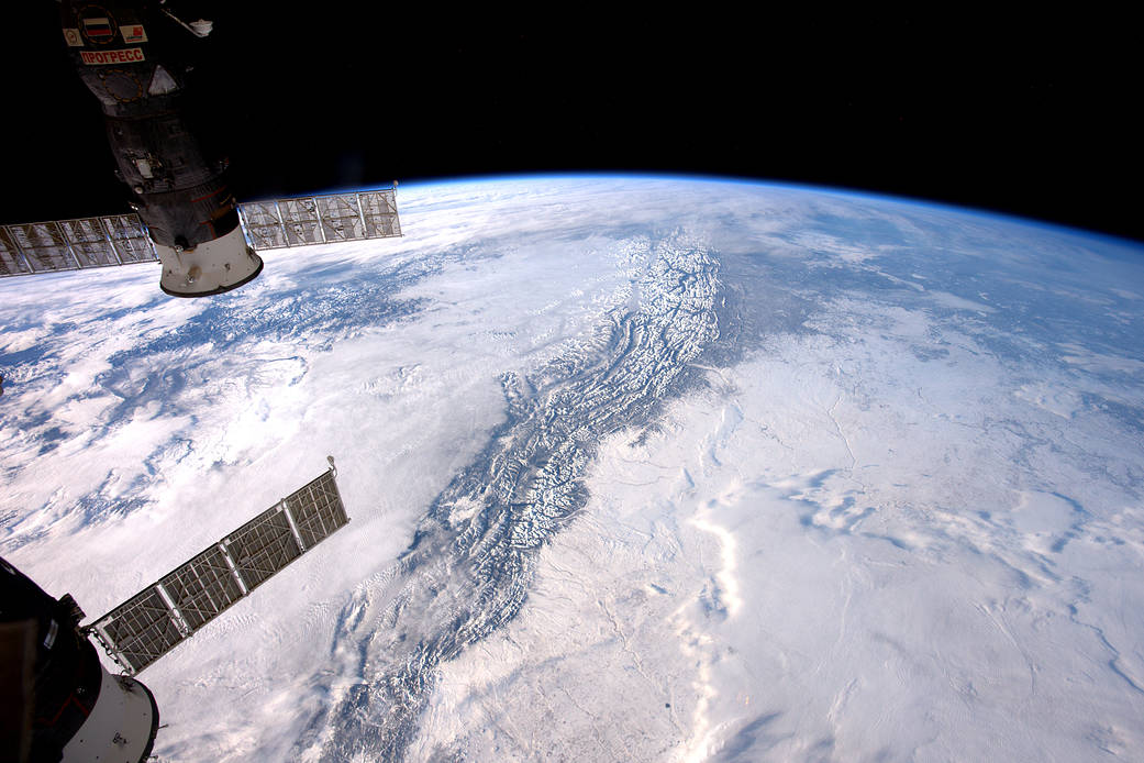 Rocky mountains visible through clouds from the International Space Station with Soyuz spacecraft visible at left of frame