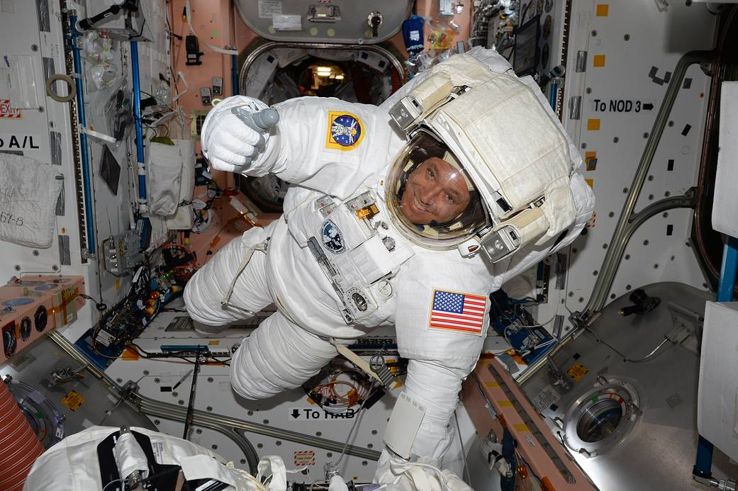Astronaut in spacesuit floats inside space station module