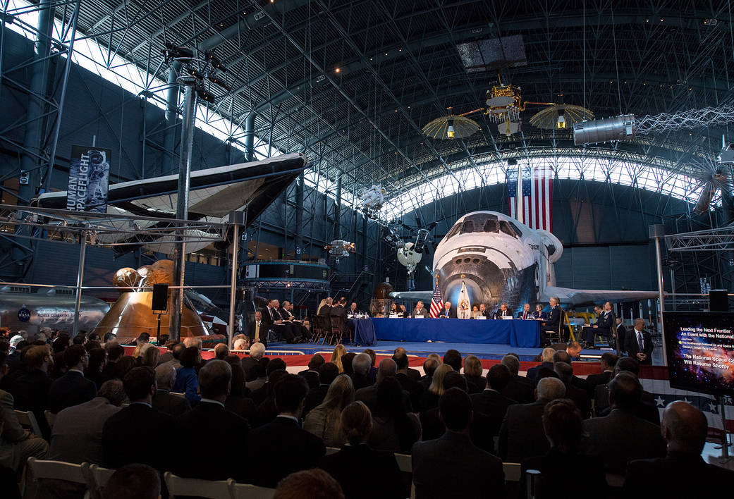 Space Council members at tables in front of Shuttle Discovery inside museum