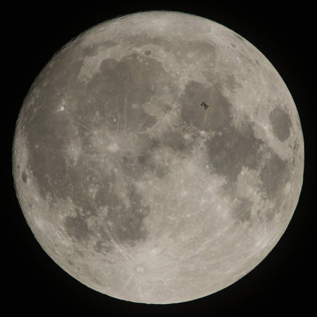 Space station seen in front of large full moon