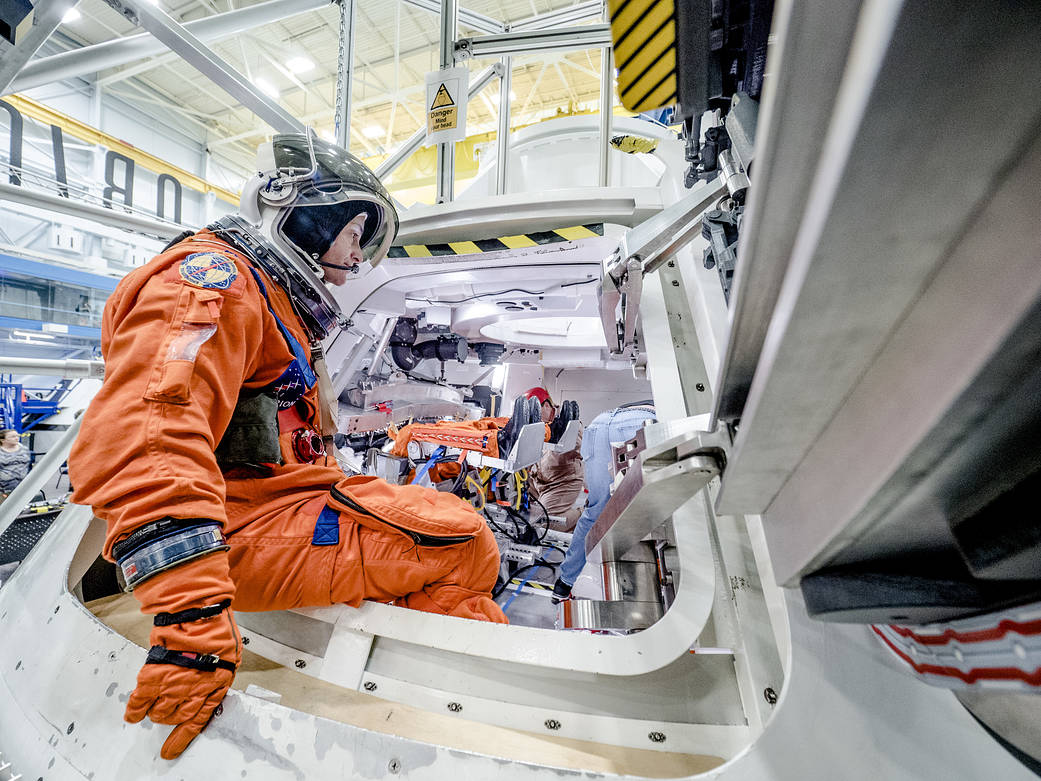 Inside a large room at Johnson Space Center, man in flight suit exits door of spacecraft