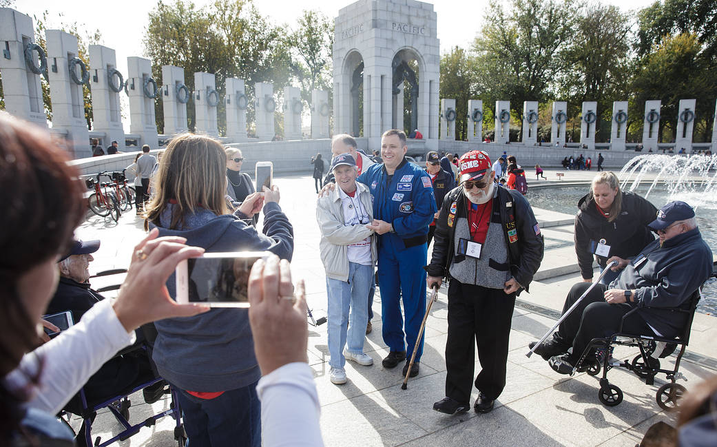 Astronaut Fischer in blue jumpsuit at World War II memorial poses for photo with veterans
