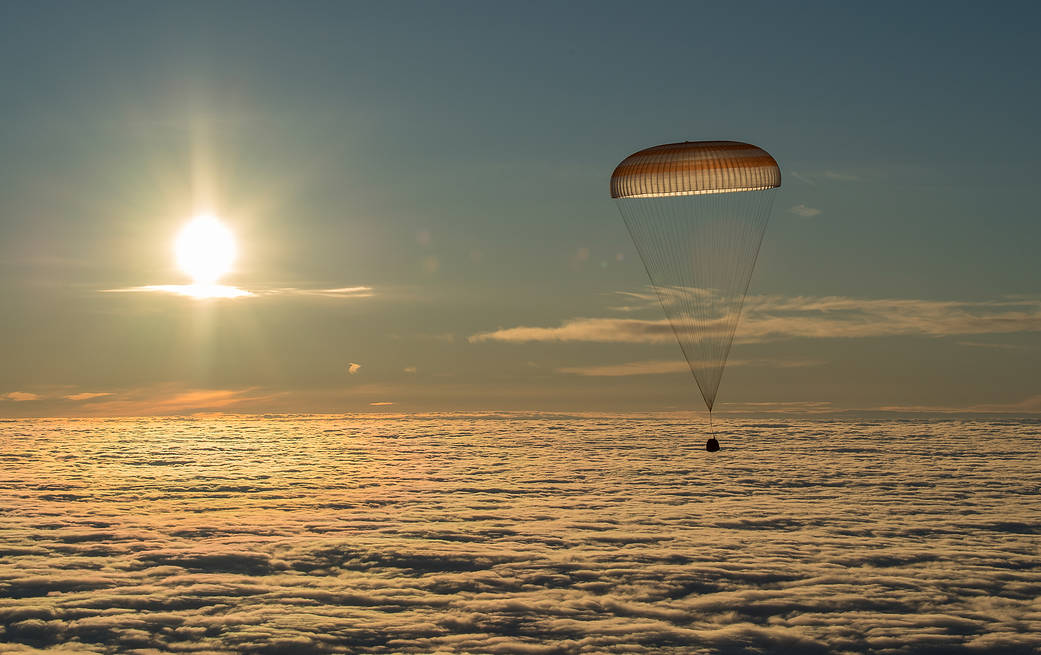 Soyuz with parachute deployed descends toward Earth with Sun in background