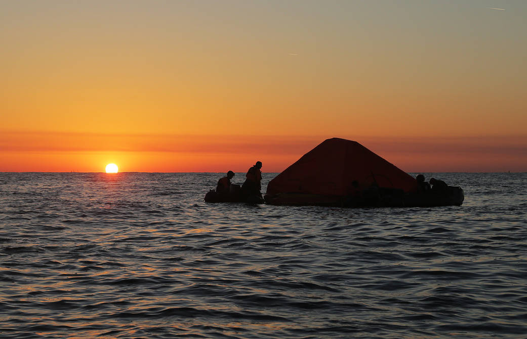 Pararescue specialists secure a covered life raft as the sun sets during an astronaut rescue training exercise