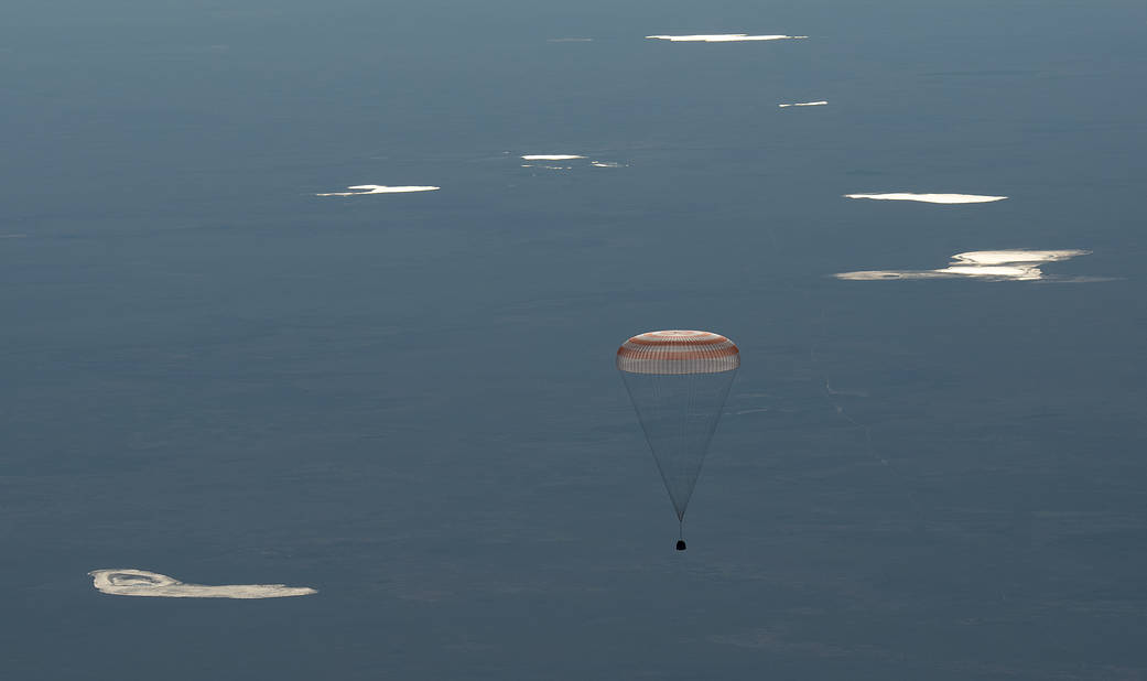 Soyuz capsule descends toward Earth with parachute deployed