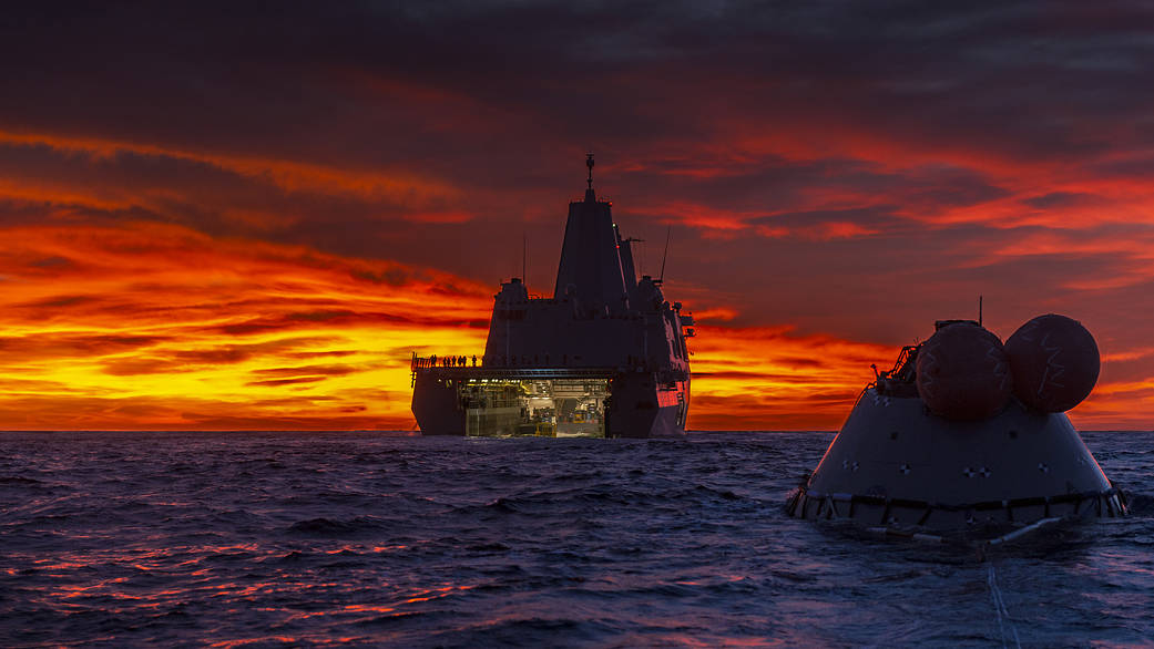 Brilliant red and yellow sunrise over the ocean with the Orion test capsule in front of the USS Murtha ship