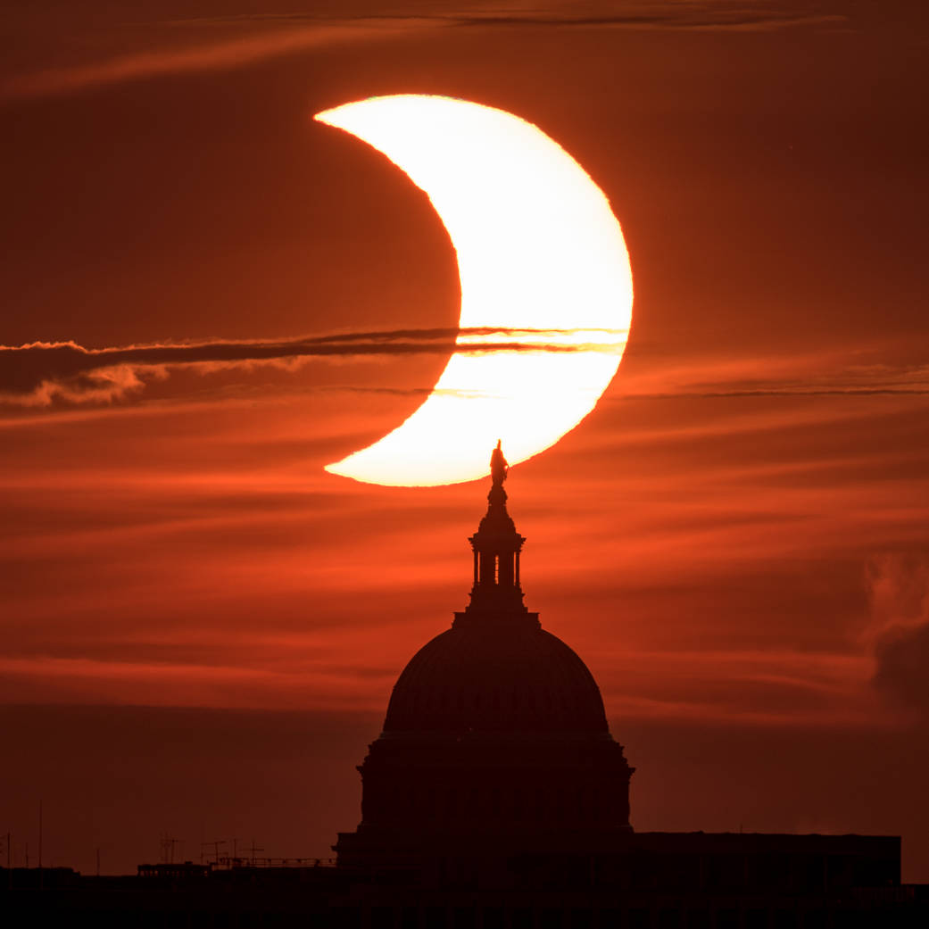 A partial solar eclipse is seen as the sun rises behind the United States Capitol Building, Thursday, June 10, 2021, as seen from Arlington, Virginia.