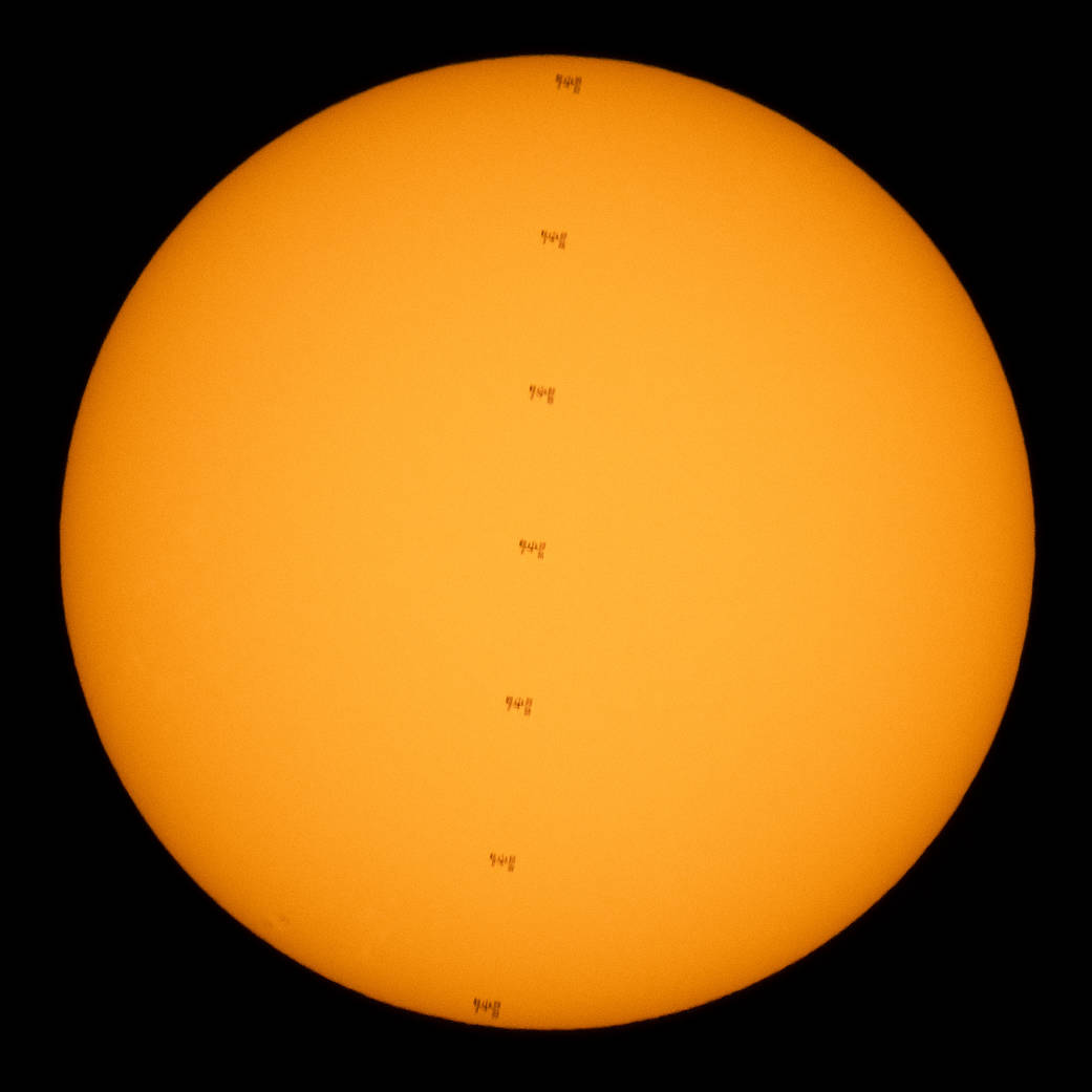 This composite image made from seven frames shows the International Space Station, with a crew of seven onboard, in silhouette as it transits the Sun