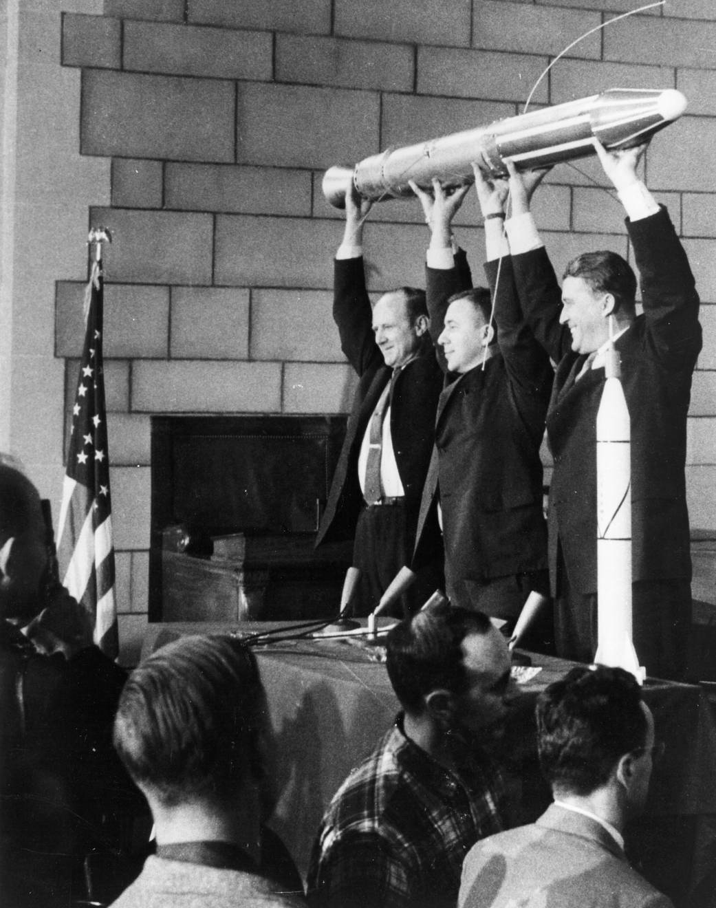 Model of Explorer 1 held up by three men at news conference