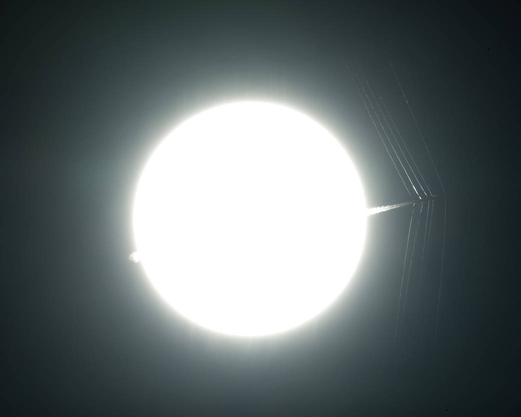 Bright sun with tip of aircraft passing in front at supersonic speed