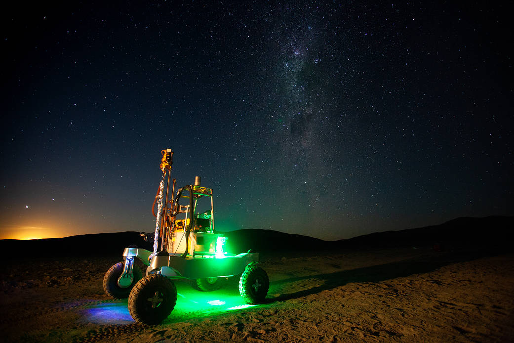 The Moon begins to rise behind the ARADS rover in Chile's Atacama Desert. The Milky Way is visible in the night sky.
