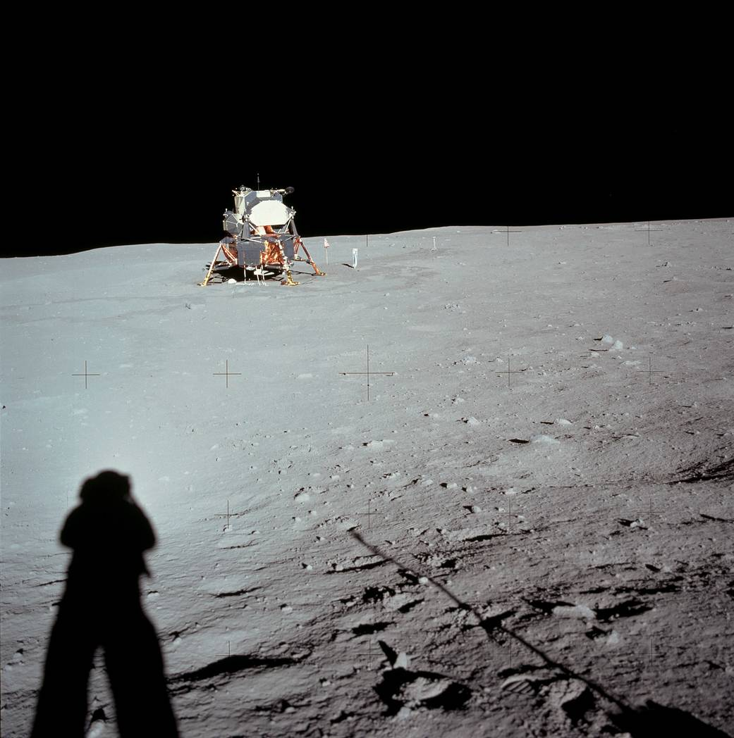 Lunar module on surface of moon with astronaut's shadow in lower left of frame