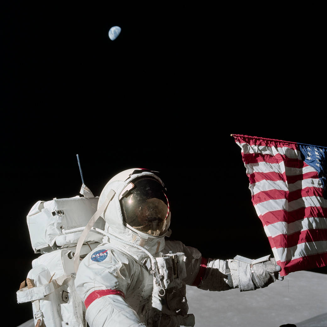 NASA caption: Apollo 17 commander Eugene A. Cernan is holding the lower corner of the American flag during the mission's first EVA, December 12, 1972. Photograph by Harrison J.