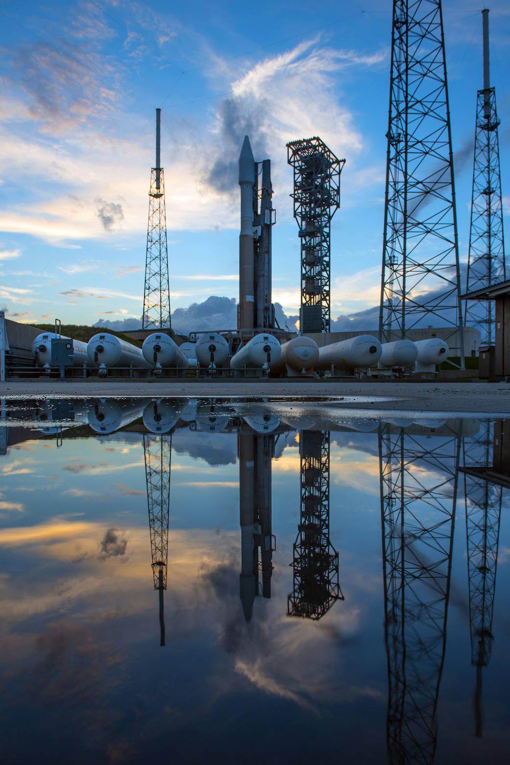 ULA Atlas V rocket with Cygnus rocket aboard at launch pad, reflected in pool of water below