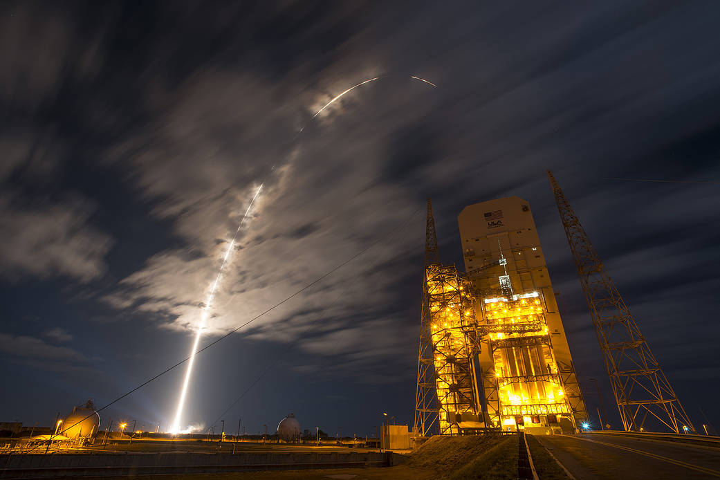 Arc of launch into clouds at nighttime with United Launch Alliance tower at right