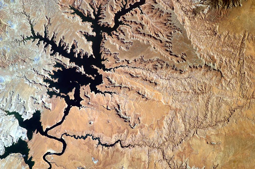 Deep blue reservoir lake and desert landscape photographed from orbit
